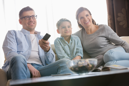 changing channels: Boy watching TV with parents in living room LANG_EVOIMAGES