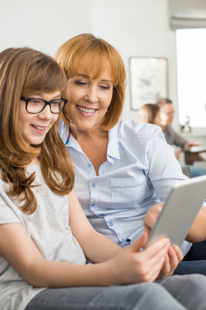 Happy mother and daughter using tablet PC with family sitting in background at home Stock Photo