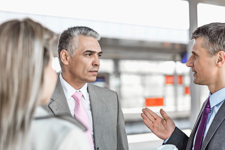 business: Businessman communicating with colleagues on railroad platform LANG_EVOIMAGES