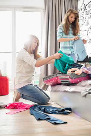 messy clothes: Sisters cleaning bedroom