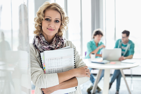 focus on foreground: Portrait of creative businesswoman holding files with colleagues working in background at office