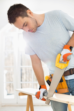Man sawing wood in new house Stock Photo