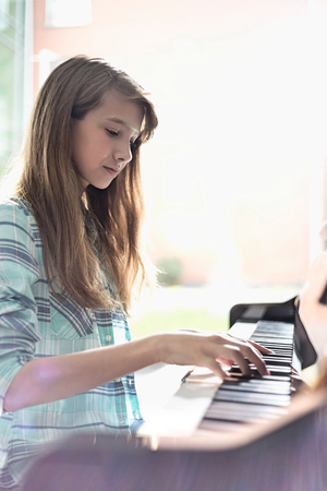 Side view of girl playing piano at home LANG_EVOIMAGES