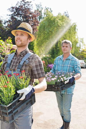 Gardeners carrying flower pots in crates at plant nursery