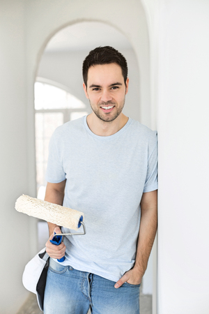 Portrait of handsome man holding paint roller in new house Stock Photo