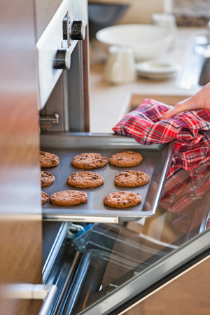 womans hand: Cropped image of womans hand removing cookie tray from oven in kitchen