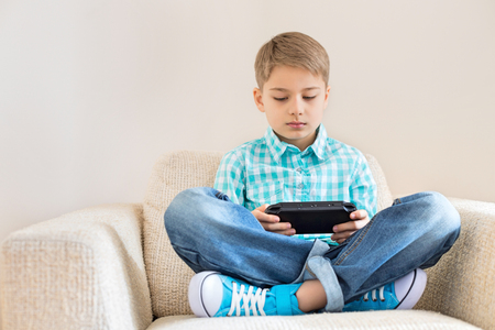 Boy playing hand-held video game on sofa Stock Photo