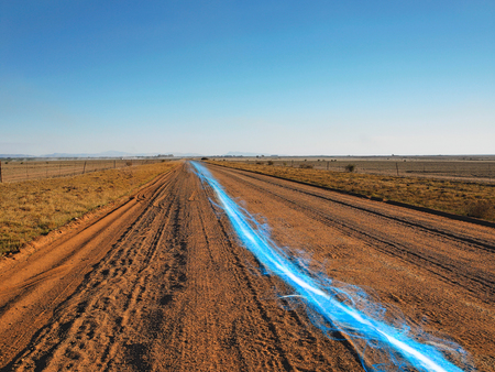 Blue streak of light on dirt road against clear sky LANG_EVOIMAGES