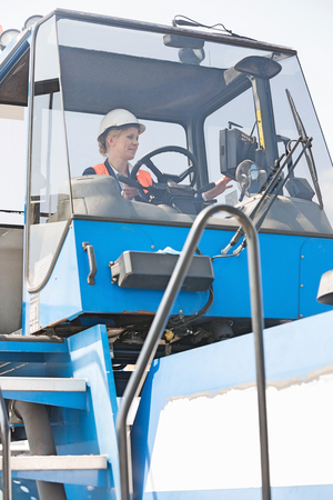Female worker operating forklift truck in shipping yard
