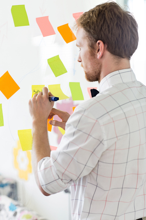 Rear view of businessman writing on sticky paper at creative office