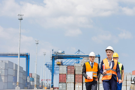 Workers walking in shipping yard Stock Photo