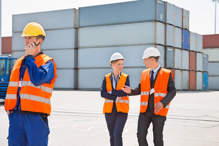 Worker using walkie-talkie while colleagues discussing in shipping yard Stock Photo