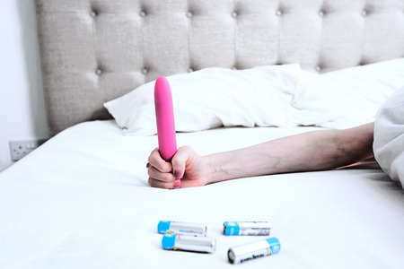 arousing: Woman holding a Pink Vibrator Dildo in Bed