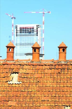 Three old chimney pot with modern construction in the background Stock Photo