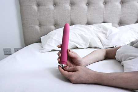 Woman inserting batteries into a Pink Vibrator Dildo in Bed