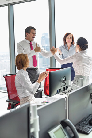 Businesspeople celebrating success in office Stock Photo