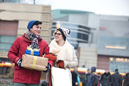 Happy couple with gifts and shopping bags walking in city during winter Stock Photo