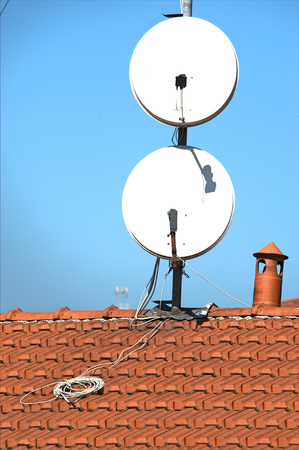 Satellite dishes on a tiled roof Stock Photo