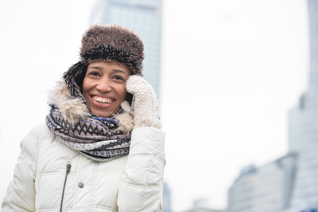 Cheerful woman in winter wear using cell phone outdoors