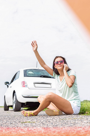 Frustrated woman hitchhiking while using cell phone on country road by broken down car