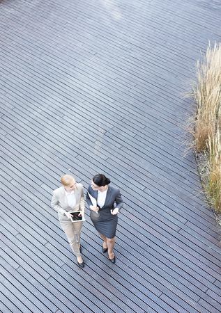 High angle view of businesswomen discussing while walking on floorboard Imagens