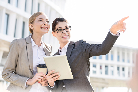 Happy businesswoman showing something to colleague while using tablet PC