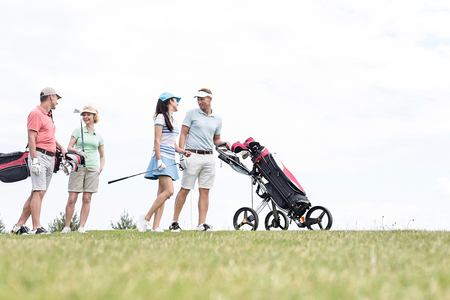 four people: Friends communicating while walking at golf course against clear sky LANG_EVOIMAGES