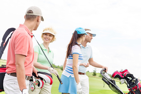 Friends talking while walking at golf course against clear sky Stock Photo