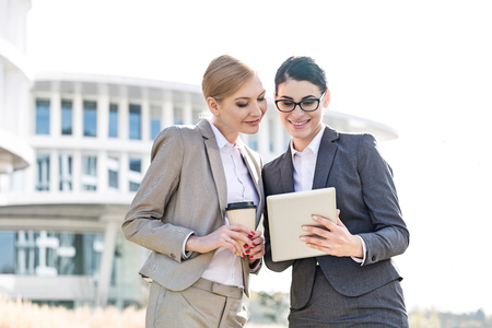 Happy businesswomen using tablet PC outside office building LANG_EVOIMAGES