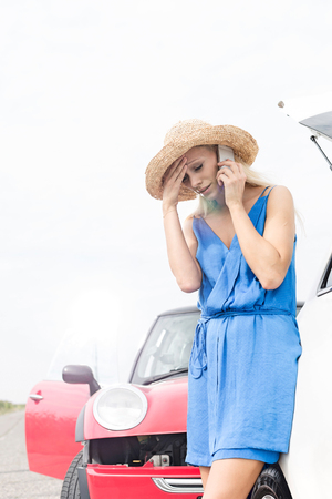 Tensed young woman using cell phone by broken down cars Stock Photo