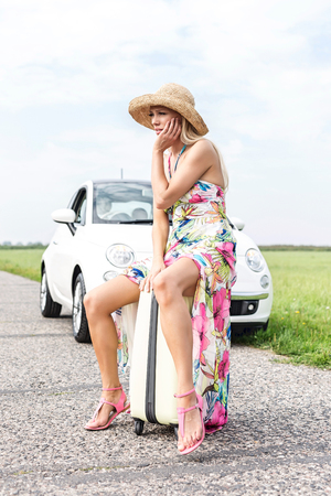 Full length of irritated woman sitting on luggage by broken down car Stock Photo
