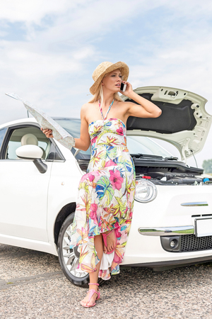 Full-length of tensed woman with map using cell phone by broken down car on road LANG_EVOIMAGES