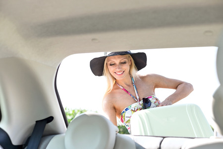 Happy woman loading suitcase in car trunk