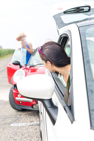 Woman looking at female crashing car on road Reklamní fotografie