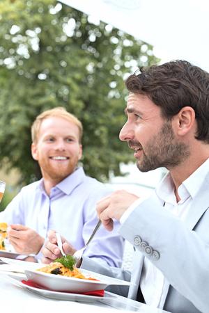 sidewalk talk: Businessmen having food at outdoor restaurant