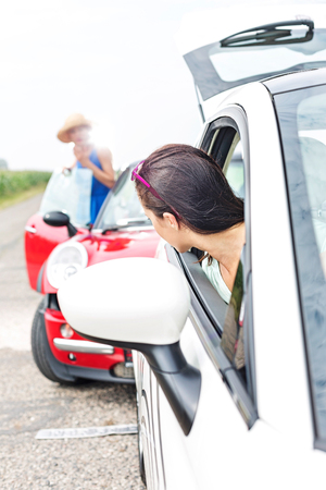 careless: Woman looking at female crashing car on road LANG_EVOIMAGES