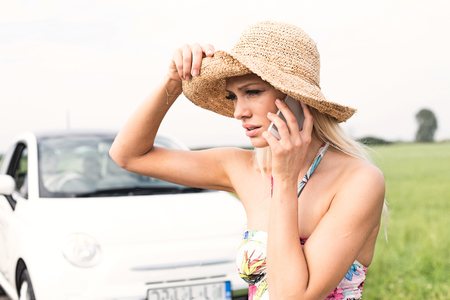 Frustrated woman using cell phone by broken down car LANG_EVOIMAGES