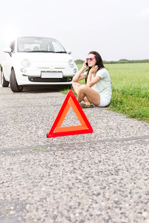 Tensed woman using cell phone while sitting by broken down car