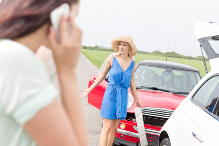 Angry woman standing by damaged cars with female using cell phone in foreground Stock Photo