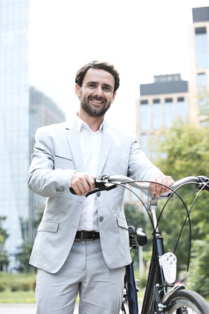 transportation: Portrait of happy businessman holding bicycle outdoors