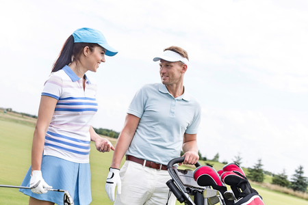 Happy man and woman conversing at golf course against clear sky