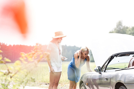 Friends repairing broken down car on sunny day Stock Photo