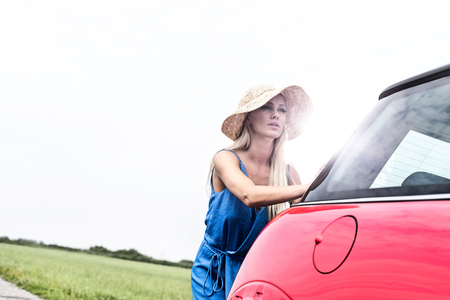 Woman pushing broken down car against clear sky Stock Photo