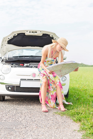 Woman reading map while sitting on broken down car at countryside Stock Photo