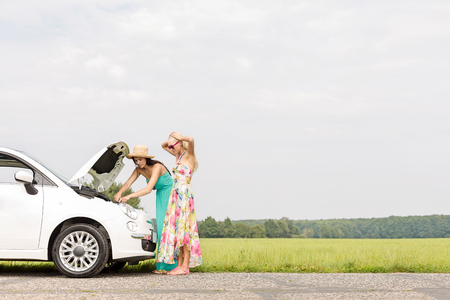 Friends examining broken down car on country road against clear sky