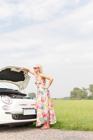 Full-length of tensed woman standing by broken down car on country road Stock Photo