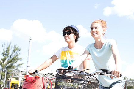 Smiling couple cycling against sky