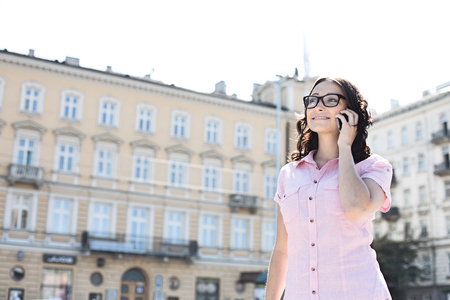 Smiling young woman answering smart phone against building on sunny day Stock Photo