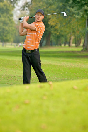 Young man swinging golf club Stock Photo