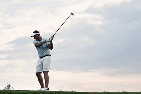 Mid-adult man playing golf against sky Stock Photo